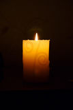 Burning candle. Burning a white candle on a dark background Stock Images