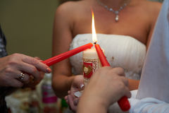 Burning a candle. Parents pass on their newlywed home through spark Royalty Free Stock Images