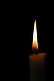 Burning candle. On the isolated black background Stock Photos