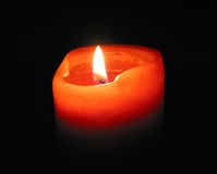 Burning candle. Red candle burning in the dark Royalty Free Stock Photography