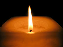 Burning Candle. A burning candle on a black background Stock Photos
