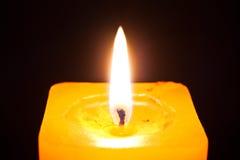 Burning candle. Close up photo of the yellow burning candle isolated on black backround Stock Photo