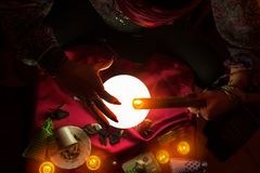 Burning candle above crystal ball. Burning candle in hands of forecast gypsy woman above crystal ball Royalty Free Stock Photo