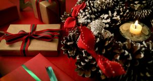 Burning candle in advent wreath and wrapped christmas gifts stock video