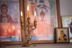 Candle against the background of orthodox icons Stock Photo