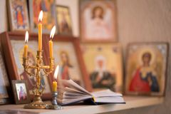 Candle against the background of orthodox icons Royalty Free Stock Photography