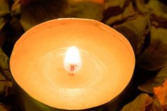 Burning candle against the background of yellow rose petals Royalty Free Stock Photos