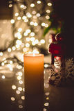 Burning candle against christmas lights Stock Images