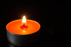 The burning candle against a dark background Stock Images