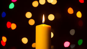 Burning Candle Against Holiday Lights Background Stock Image