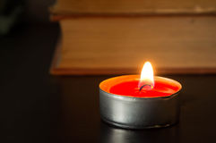 The burning candle against the old book Royalty Free Stock Image