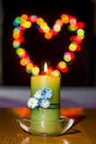 Burning candle amid colorful  Bokeh Royalty Free Stock Photography