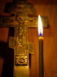 Burning candle and ancient Christian cross Royalty Free Stock Image