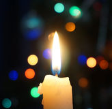 Burning candle on a background of Christmas lights Stock Photo