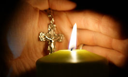 Burning candle on background of hands with cross Royalty Free Stock Image