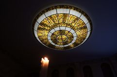 Burning candle on the background of the round ceiling. Indoor lighting royalty free stock image