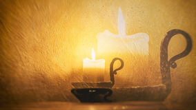 Burning candle on a background of textured walls Stock Photos