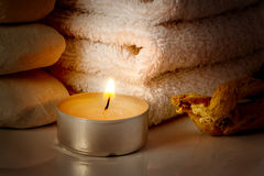 Burning candle on a background of white towels. Restful image of burning candle on a background of white towels Stock Photos