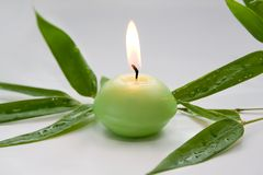 Burning candle and  bamboo leaves Stock Photo