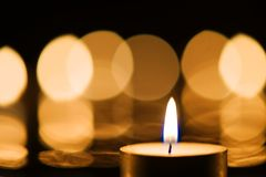 Burning candle with beautiful bokeh background. Close-up of a burning candle against bokeh background Royalty Free Stock Photos