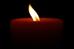 Burning Candle on Black Background. A photograph of a burning candle with a full, curved flame on a black background Stock Image