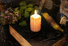 Burning candle on black magic book. Textured and filtered Halloween image with bloody candle on black magic book Stock Photos