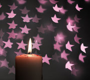 Burning candle with blur pink stars on black background Stock Photo