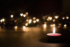 Burning candle with bokeh hearts Royalty Free Stock Photos