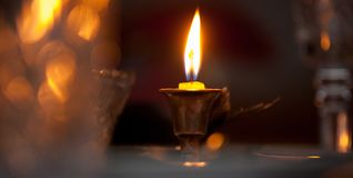 A burning candle in a bronze candlestick on a festive table with stock images
