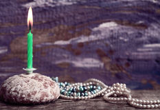 Burning candle, cake, pearls, purple background Stock Images