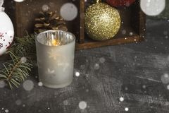 Burning candle in candlesticks and Christmas attributes on a dar. K background. Copy space. Snow Royalty Free Stock Photos