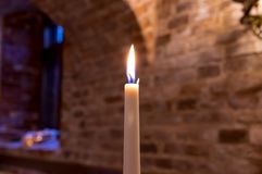 A burning candle in the castle stock photography