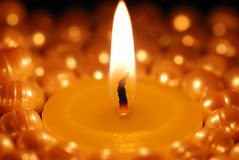 Burning candle in the centre of pearls Stock Image