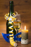 Burning candle with champagne and serpentine, mask Royalty Free Stock Photo