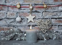 Burning candle and Christmas decoration in front of brick wall Royalty Free Stock Photography