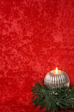 Burning candle with Christmas decorations Stock Photos