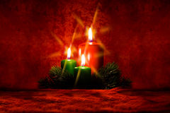 Burning candle with Christmas decorations. Of the cross filter effect Stock Image