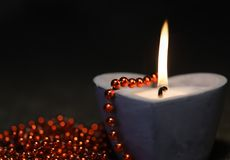 Burning candle with christmas lights as background Stock Images