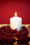 Burning candle for christmas. Lit candle for christmas on red background Stock Photography