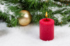 Burning candle with Christmas objects covered with fresh snow Stock Photos