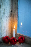 Burning candle and Christmas ornaments Stock Images