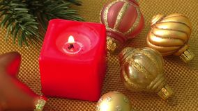 Burning candle in a Christmas setting with seasonal decorations stock footage