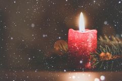 Burning candle on Christmas tree background. Red burning candle on Christmas tree background stock photography