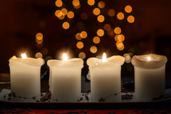 Burning candle with christmas tree bokeh Stock Image