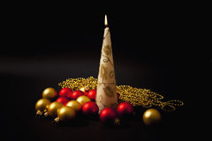 Burning candle with christmas-tree decorations Stock Image