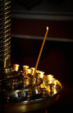 Burning candle in the church. Illuminated by sun Royalty Free Stock Image