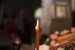Burning candle in the church in front of the icons Royalty Free Stock Image