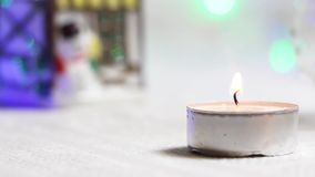Burning candle close-up against the backdrop of a New Year`s house and twinkling lanterns stock video footage