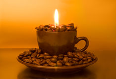 Burning candle and coffee beans Stock Photos