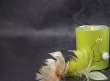 Burning candle with rabbit covered with colorful feathers on concrete background. Burning candle covered with colorful feathers on concrete background royalty free stock photo